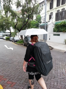 Nic with her female focused, Berghaus backpack- rain cover on due to a Singapore drizzle. The weird shape on the left is due to walking poles. Photo by Steve Collier, 2015.